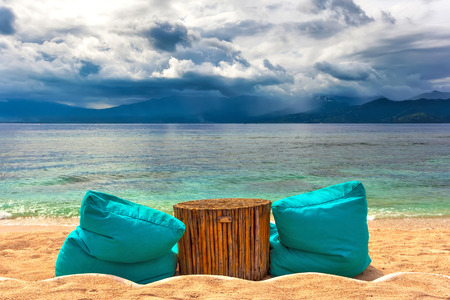 Soft ottomans around a wooden bamboo table on a sunny beach against the background of the Bali Sea and the approaching rain clouds on the shore of another island. Gili Trawangan, Indonesia. Stock Photo