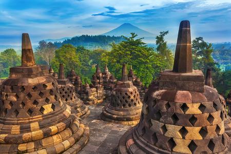 Candi Borobudur는 열대 우림, 아침 안개와 Sumbing Mountain의 배경에 있습니다. Candi Borobudur, Yogyakarta, Jawa, 인도네시아.