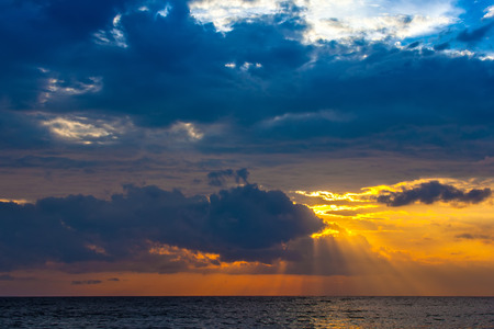 A bright colorful orange sun makes the rays through the dense blue clouds on the Bali Sea. Sunset on the Lombok island, Indonesia. Imagens