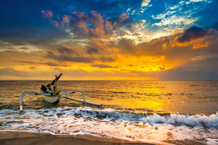 A fishing boat goes to the ocean in the evening. Bright colorful orange sun in the dense blue clouds over the Bali Sea. A white wave pours a foam to the sandy beach. Sunset on the Lombok Indonesia