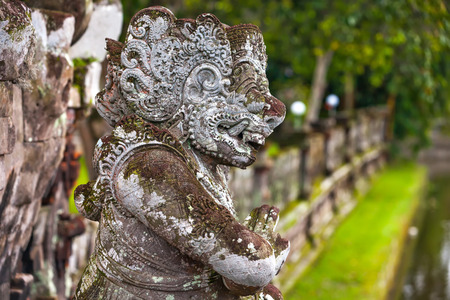 Guard demon statue in front of the entrance to the temple against the background of a wall and a pond. Copy space for text. Taman Ayun Temple of Mengwi Empire, Badung regency, Bali, Indonesia.