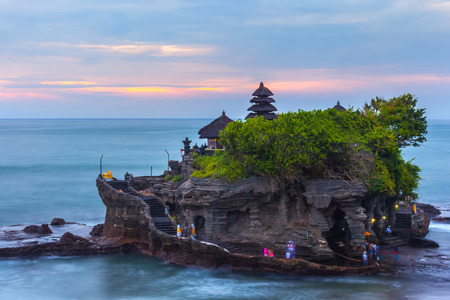 The Pilgrimage Temple of Pura Tanah at sunset, island with an Indonesian shrine on the ocean, long exposure, copy space for text. Tanah Lot Temple, Beraban, Bali, Indonesia.