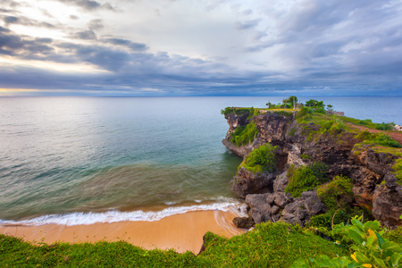 over the edge: Volcanic green rock with huge stones, on the sea shore, against the backdrop of beach sunset. Beautiful blue clouds on the horizon. Balangan beach view, Jimbaran, South Kuta, Bali, Indonesia.