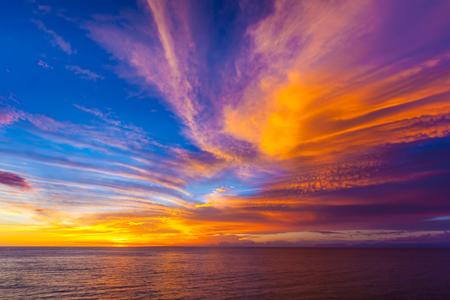 cirrus: Stunning colorful sunset, blue sky, yellow purple cirrus clouds, orange sun, dark sea. Sunset on Jimbaran, South Kuta, Bali, Indonesia.