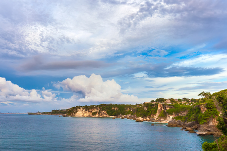 kuta: Panorama of the rocky tropical coast, cliffs and stones, green forest and house on the shore, against a background of large cumulus clouds. Coastline of Jimbaran, South Kuta, Bali, Indonesia.