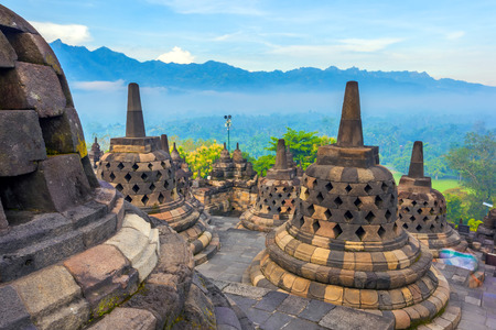 Candi Borobudur in the background of the rainforest, morning mist and Sumbing Mountain. Candi Borobudur, Yogyakarta, Jawa, Indonesia.