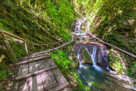 Waterfall in a green spring forest surrounded by a ladder railing and railing, summer natural landscape. 33 Waterfalls, Sochi, Russia. Stock Photo