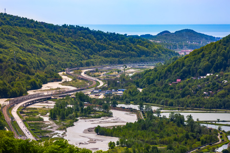 High-speed highway next to the mountain river, green spring forest around the fishing trout farms on the background of the Black Sea on the horizon. The road Adler Krasnaya Polyana, Sochi, Russia. Stock Photo