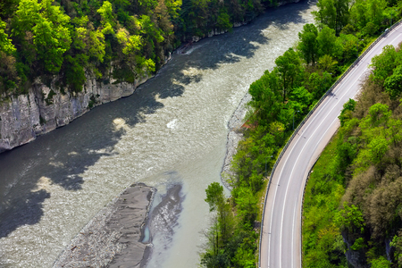 Highway in a green forest next to a mountain river between the rocky mountains, top view, aerial photography. The road from Adler to Krasnaya Polyana, Sochi, Russia. Stock Photo