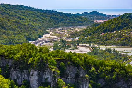 High-speed highway next to a rocky mountain with a green spring forest around a trout fishermens farm in the background of the Black Sea on the horizon. The road Adler Krasnaya Polyana, Sochi Russia. Stock Photo