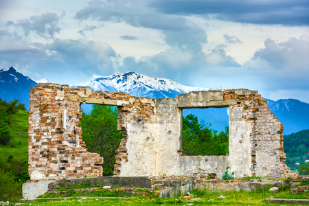White brick wall of a ruined house without a roof on the background of a snow-capped mountain in the green spring. Rural spring landscape in Sochi, Russia.