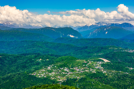 The view of the highland village and Caucasus mountains covered with green forest and snow from the lookout tower on mount Akhun. Khosta district, Adler, Sochi, Russia.
