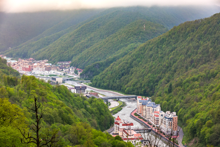 Aerial view of the hotel complex on the banks of the Mzymta river in the spring foggy morning, multi-storey modern buildings in a mountain resort. Rosa Khutor Alpine Resort, Sochi, Russia - May, 2016. Standard-Bild