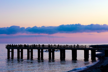 Silhouettes of fishermen with fishing rods on the pier on the background of a twilight sunset pink color on the beach. Pier on the Black Sea coast, Sochi, Russia.