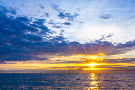 The bright rays of the yellow sun and the evening on the shore. Beautiful colorful sunset on the Black Sea, Sochi, Russia.