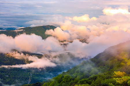 The mountain valley is covered with a spring green forest with rare clouds and fog on the background of a cloudy sky. Panorama of the Caucasian mountains from the observation tower on Mount Akhun.