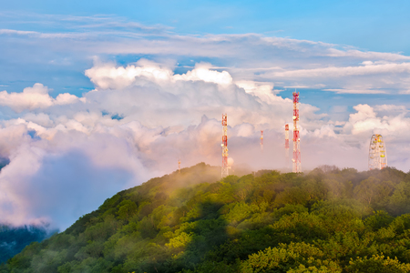 The mountain covered with a spring green forest, in which there are honeycomb towers and a Ferris wheel in a huge cloud. Panorama of the Caucasian mountains from the observation tower on Mount Akhun. Stock Photo