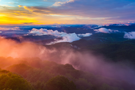 Sunset hidden behind clouds and fog over hills, bright yellow sun on colorful cloudscape, blue violet orange sky. Panorama of the Black Sea coastline from Akhun mountain, Big Sochi, Russia.