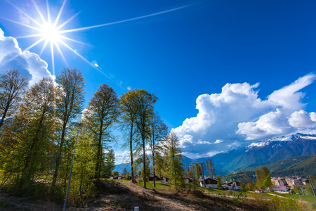 Mountain modern village with rare trees against the backdrop of the bright sun casting its rays on the blue sky with white clouds and snowy peaks of the mountains. Spring landscape, Sochi, Russia. Stock Photo