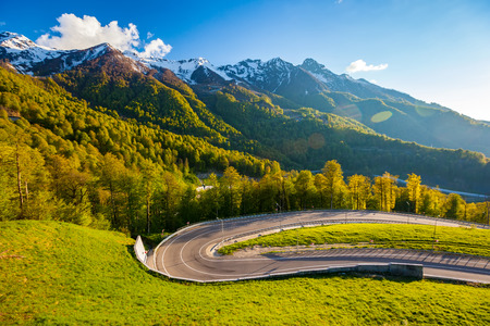 A winding modern asphalt road to the top of the au pair in the bright yellow rays of the evening sun, dense forest and the Caucasian mountain range. Summer spring forest mountain landscape, Sochi Russia. Stock Photo