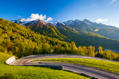 A winding modern asphalt road to the top of the au pair in the bright yellow rays of the evening sun, dense forest and the Caucasian mountain range. Summer spring forest mountain landscape, Sochi Russia. Banco de Imagens