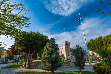 Stone Church of the Annunciation with the city clock on the tower on the Evaggelistrias Square among the beautiful green trees and the developing flag. Volos, Magnisia, Hellas, Greece - April 2017.