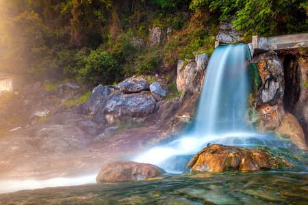 The stream of water in the waterfall and fall on stones with green moss and algae at dawn. Thermal springs Loutra Thermopilon, Greece.