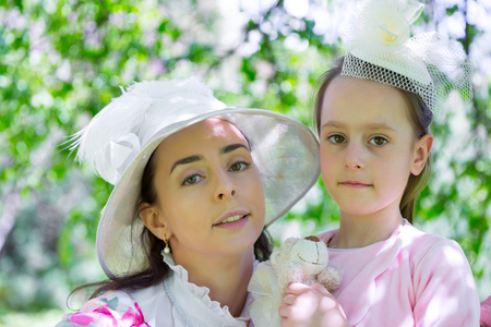 A close-up portrait of a family, two ladies of different generations in a beautiful vintage white hats with a toy in their hands are pressed against each other. Mother and daughter in a summer park. Imagens