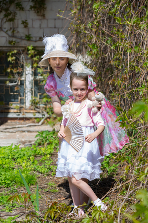 Ladies in vintage clothes posing near a vertical greened wall. A white pink green dress, a hat, a fan, beads made from imitation jewelry and a toy bear. Mother and daughter in a summer park.