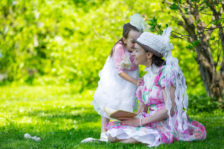 A little girl hurries to share secrets with her mom in the background in a bright sunny park on the green field in beautiful white classic aristocratic dresses. Mother and daughter in a summer park.