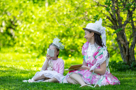 Family idyll, sitting on a green grass in a sunny bright park in a beautiful light vintage dresses in beads and hats, reading books and fooling around together. Mother and daughter in a summer park. Stock Photo