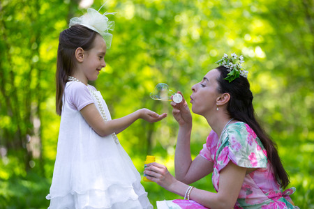 Mother playing with her daughter, launches soap bubbles in a sunny green park, closeup of fun and joy. White vintage dress with hat and costume jewelery. Family in a summer park. Imagens