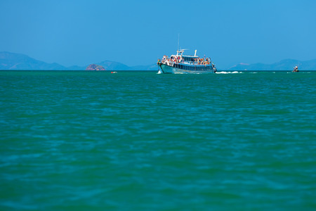 The passenger ship is on the waves in the sea, many people stand on the deck, sit on the stairs and enjoy the views.