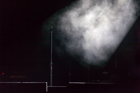 Microphone holder standing on a black dark scene, smoke illuminated by white spotlight at the side, below are stage monitors.