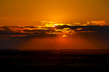 Dark orange sunset, the sun disc hides behind the clouds in the middle of the frame, casts shadows on the valley with silhouettes of fields and forests.