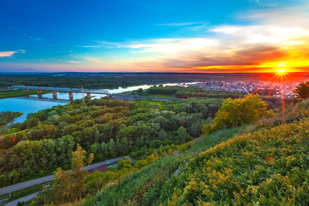 Bright red yellow orange setting sun on a blue sky from a hillside, the valley of the Belaya river in a green dense forest and a metal railway bridge.