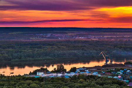 Bright red yellow orange setting sun on a blue sky with dramatic dark clouds over the city on the banks of the Belaya River in a green dense forest.