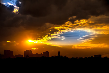 Bright colorful blue sky through yellow rain clouds with a silhouette from the rays of the sun in the evening in the dark at sunset in the city.