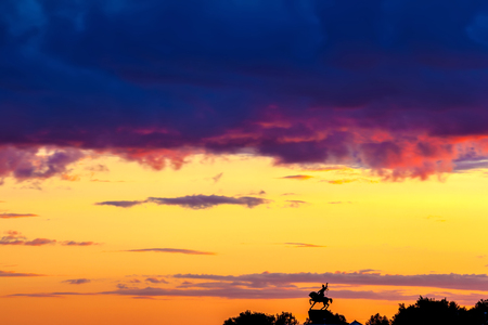 Silhouette of monument to Salawat Yulaev, folk hero on a horse against a bright yellow purple violet sky with clouds and orange sun disk at city sunset.