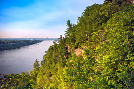 A large cliff overgrown with green grass and trees dominate over the White River in the evening at dusk during sunset under a clear blue sky.