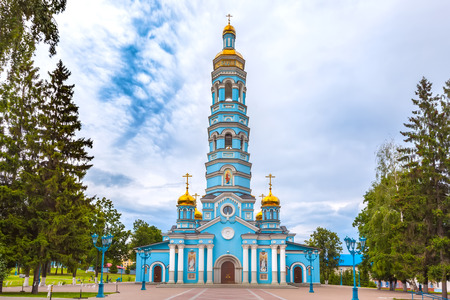 Light blue high church with golden domes surrounded by green trees under large rain clouds on the square. Reklamní fotografie