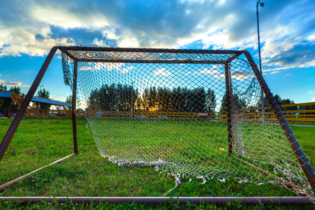 A small football goal with a torn net on green grass against a blue sky with white clouds and a yellow sun hiding behind the trees. 版權商用圖片