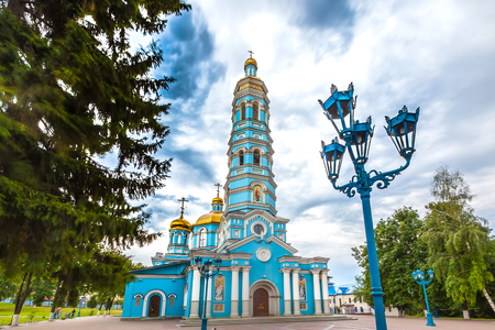 Light blue high church with golden domes surrounded by green trees under large rain clouds on the square.