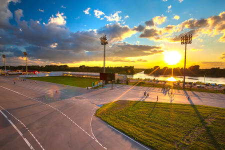 People walk, rollerblading and biking in the biathlon stadium at sunset in the bright yellow rays of the sun on the banks of the river.