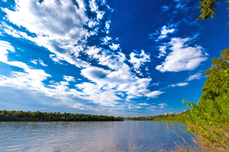 Belaya river bank, overgrown with lush shrubs and green trees under colorful white clouds against the blue sky against the background of urban buildings in the distance. 版權商用圖片