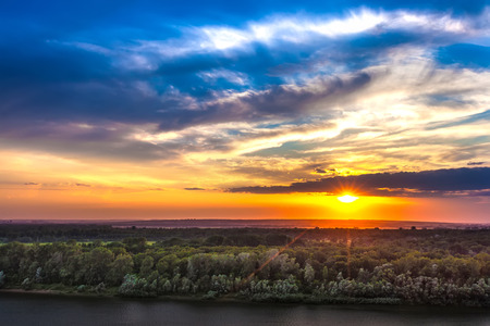 Incredibly beautiful colorful sunset on the river bank, bright orange sun hidden behind white clouds on a saturated blue sky above the green forest.