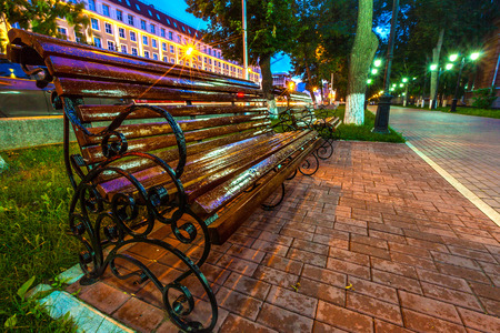 Brown wooden cast-iron varnished bench, drops after rain in the lights of the night city on a tiled pedestrian walkway.