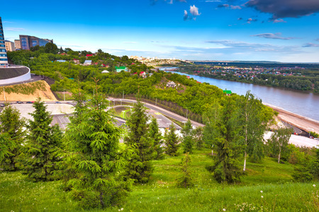 Green trees on the slope in front of the panorama of the city and the river flowing below on a bright sunny day. Multicolored private houses. 版權商用圖片