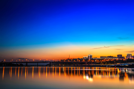 Belsky bridge over the river after sunset at night in the bright orange lights of the city with reflection in the water and a clean colorful blue sky at dusk.