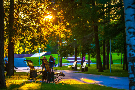 The benches in the urban green park are illuminated by the bright yellow orange sunset sun through the branches of the trees, people walk along the paths.